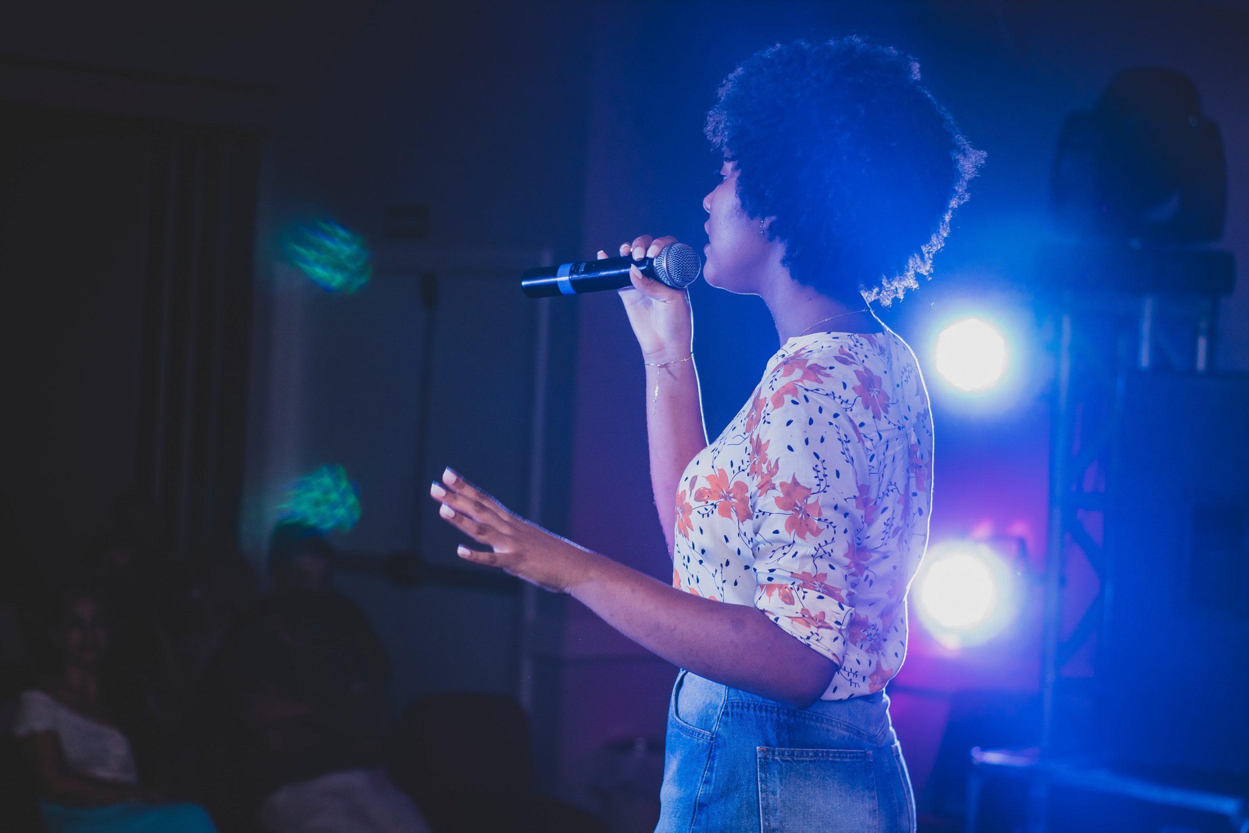 Mujer de cabello rizado cantando en karaoke