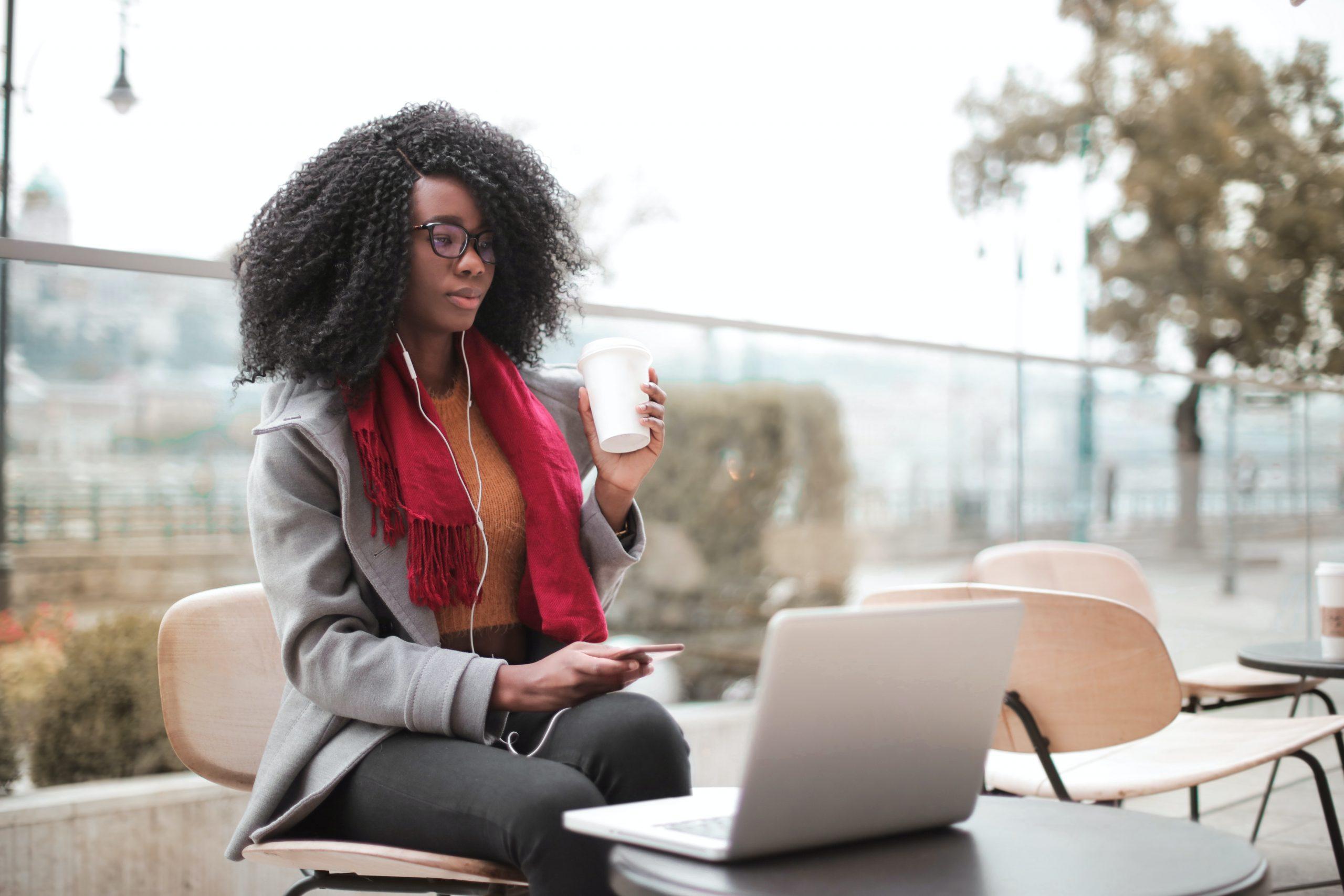Mujer bebiendo café mientras trabaja al aire libre y con la otra mano sostiene un móvil