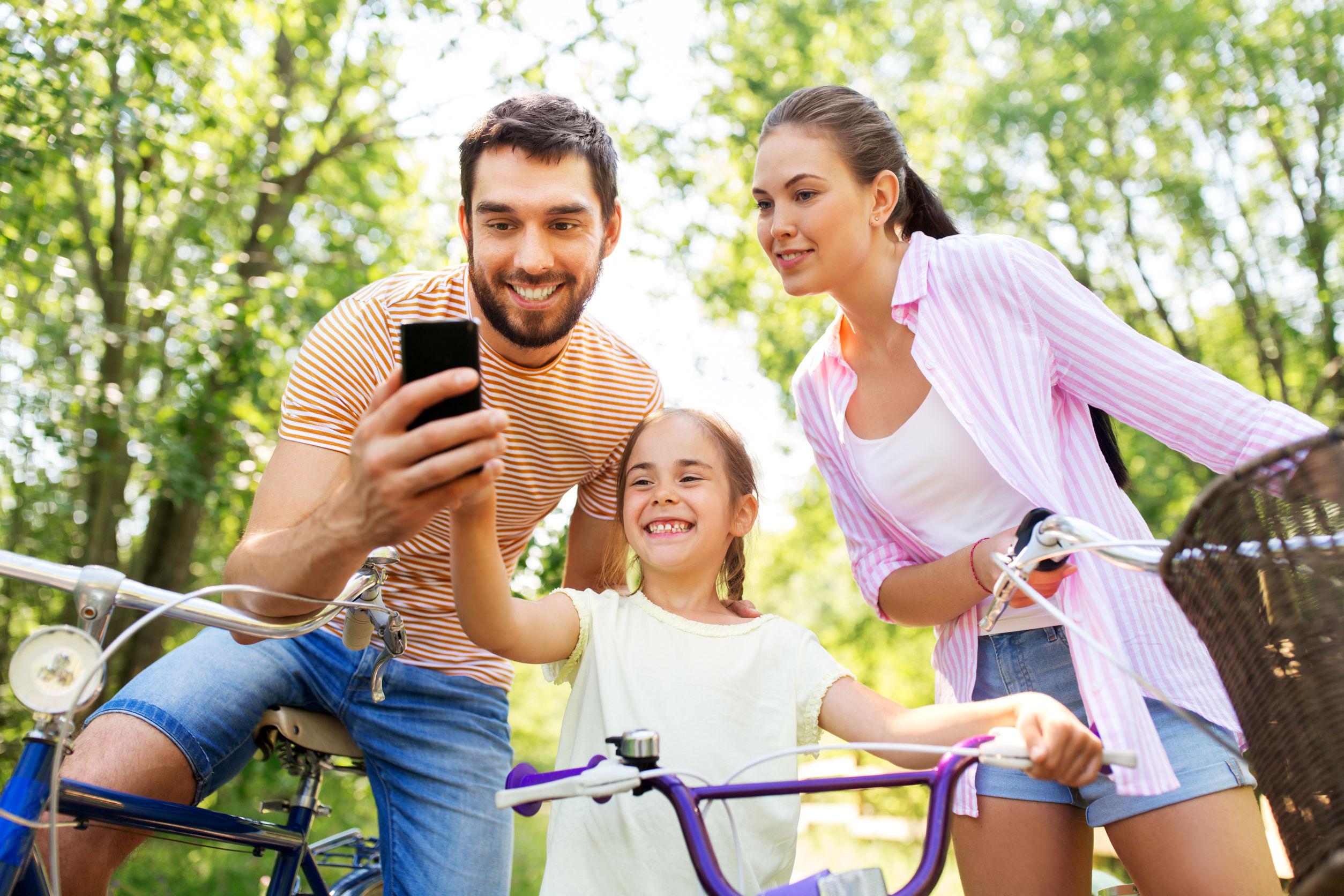 madre, padre e hija pequeña con teléfono inteligente y bicicletas en el parque en verano