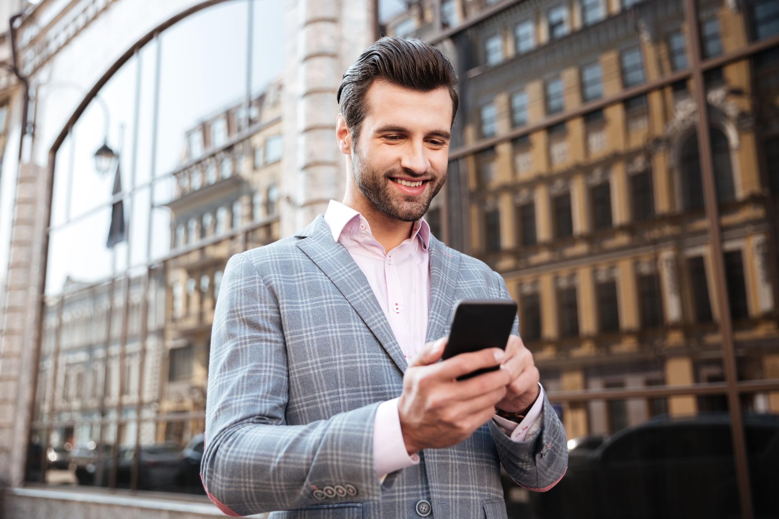 Joven sonriente en chaqueta mirando el teléfono móvil en una zona de la ciudad