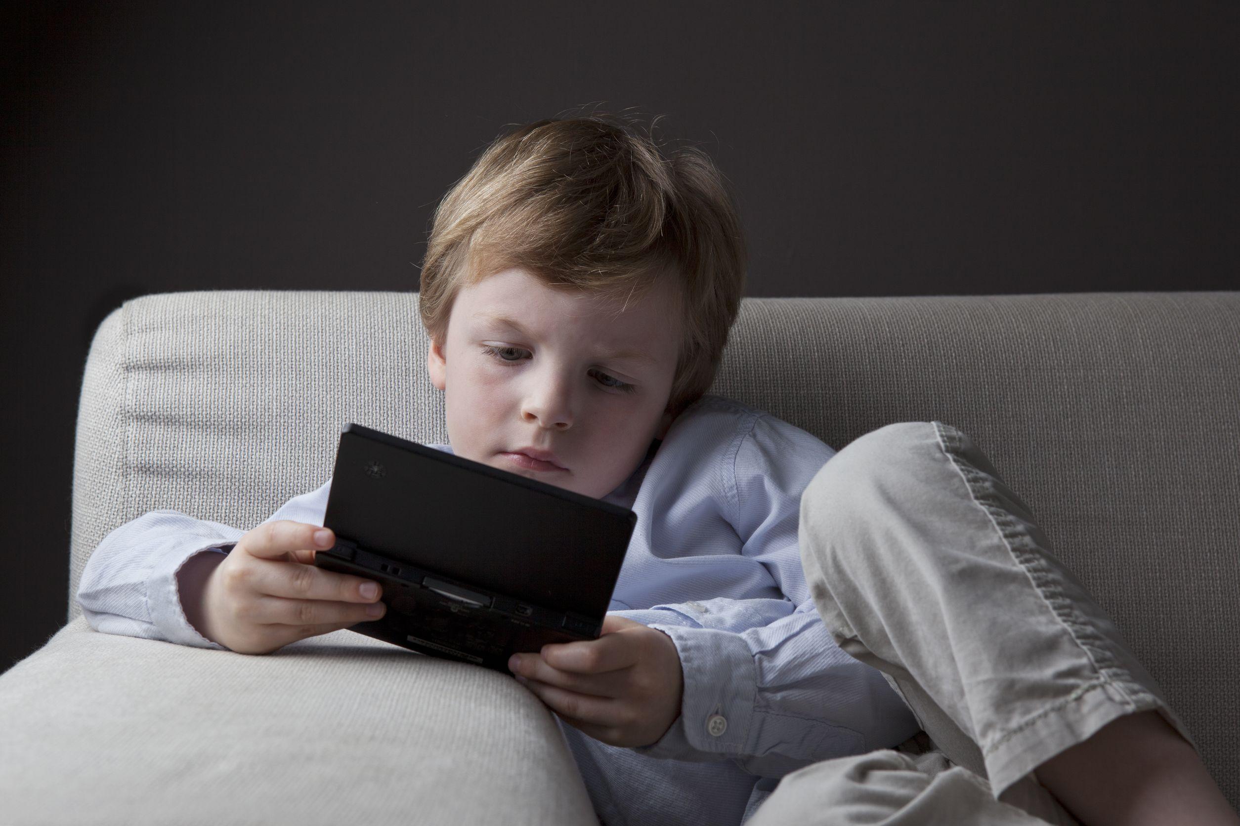 Niño sentado jugando videojuegos