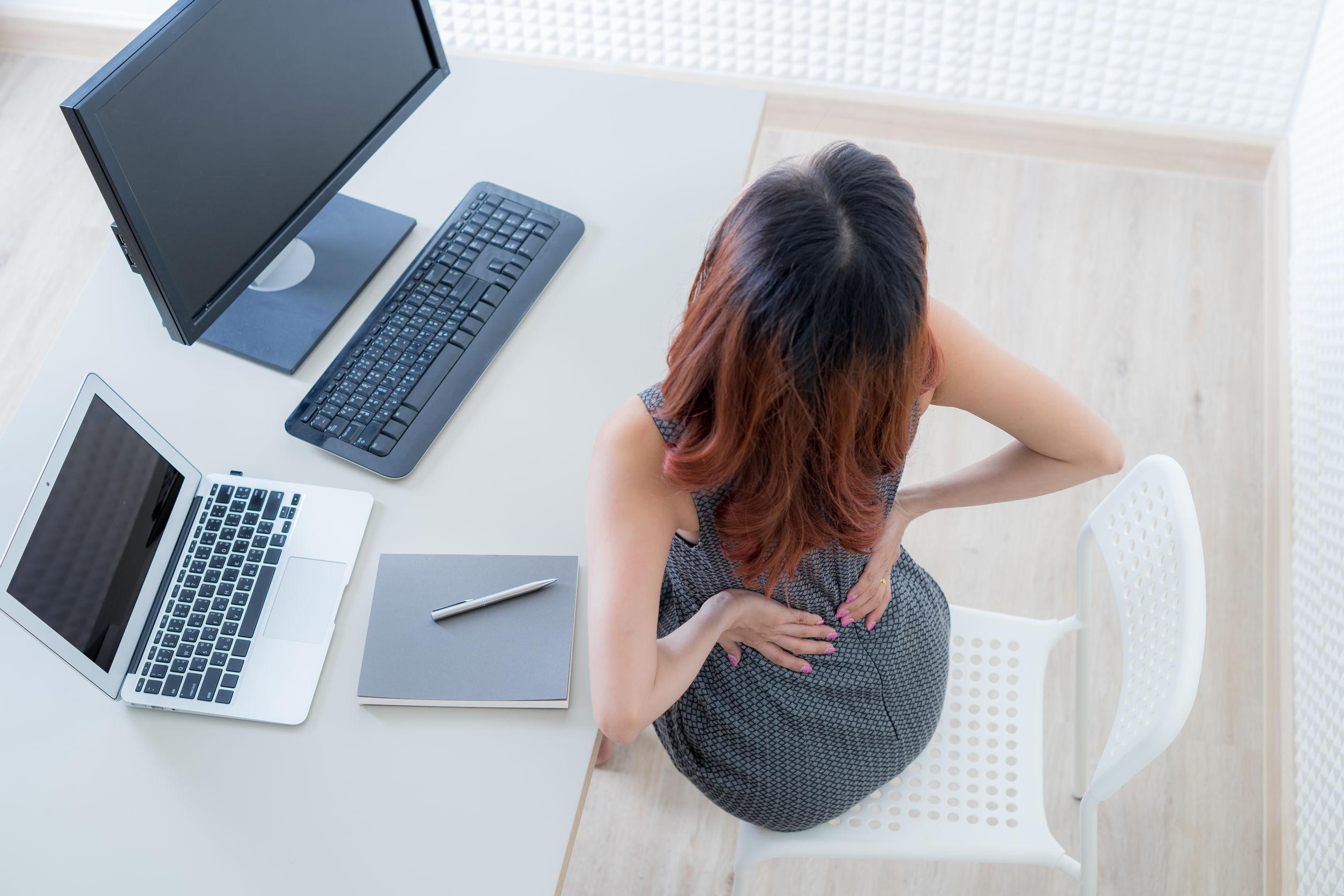 Mujer de negocios con dolor de espalda