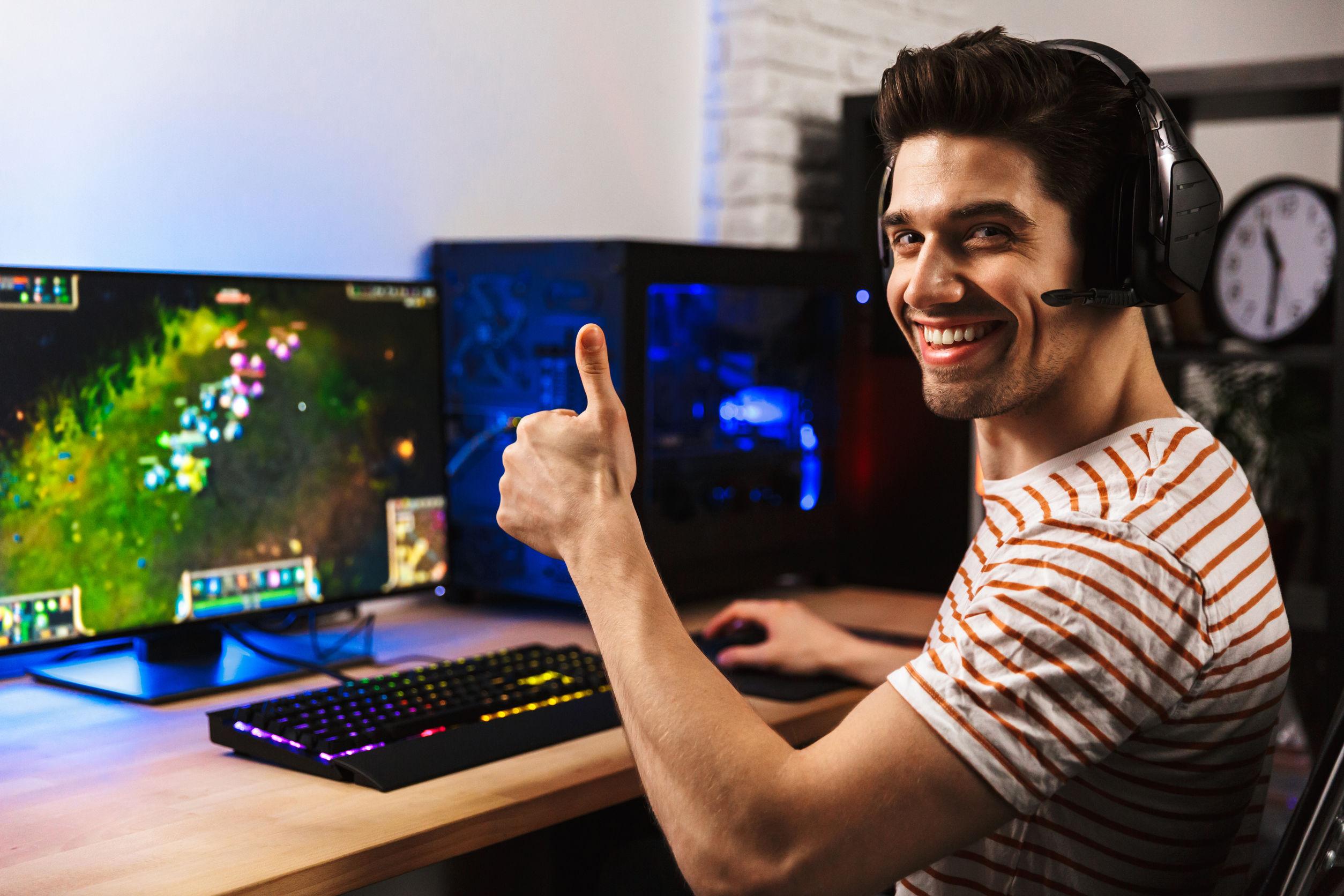 alegre chico jugador en auriculares jugando videojuegos en la computadora y mostrando el pulgar hacia arriba